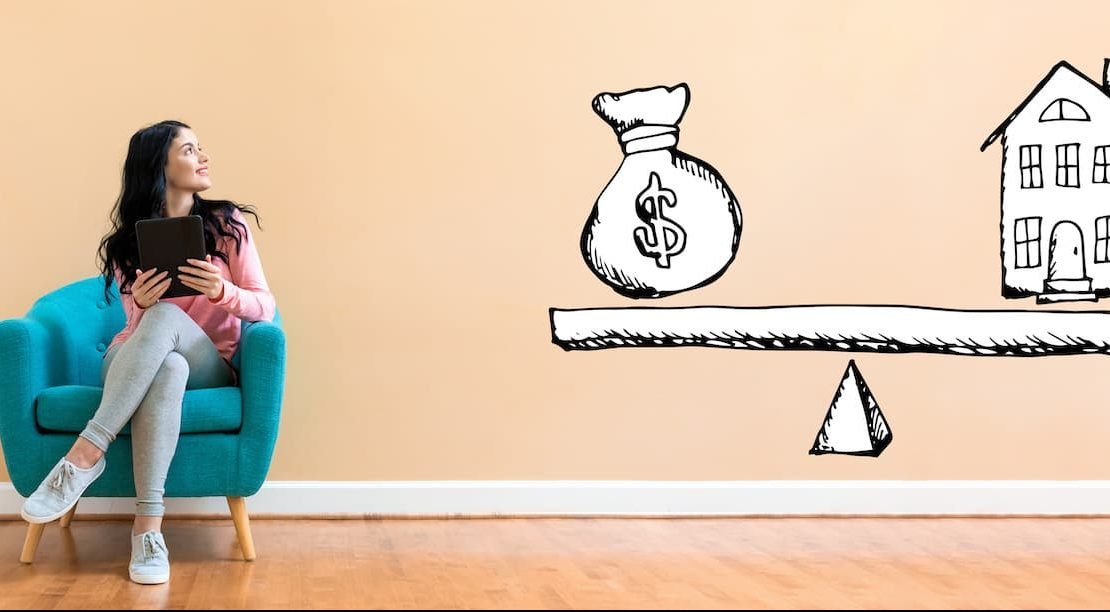 House and money on the scale with woman using a tablet